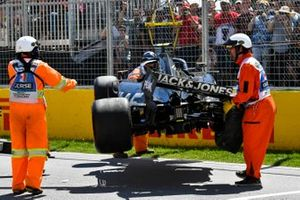 Marshals remove the damaged car of Kevin Magnussen, Haas VF-19, from the circuit