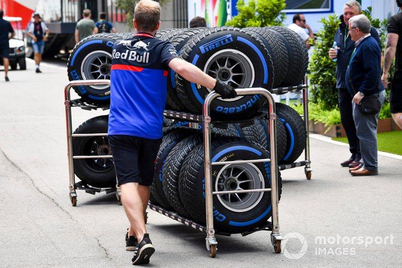 Un mécanicien Toro Rosso avec des pneus pluie dans le paddock