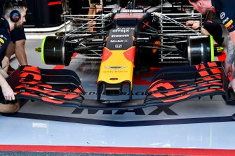 Mechanics fit a front wing to the car of Max Verstappen, Red Bull Racing RB15