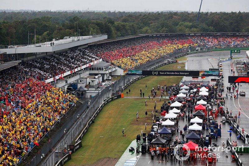 Todos los coches en la parrilla con fans con la bandera alemana