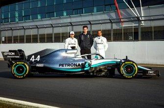 Гонщик Mercedes AMG F1 Валттери Боттас, руководитель команды Тото Вольф и пилот Льюис Хэмилтон рядом с автомобилем W10