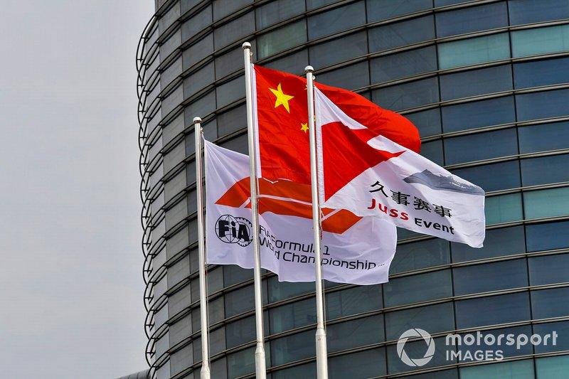Una bandera china junto a una bandera de Fórmula 1 de la FIA y una bandera de evento de Juss.