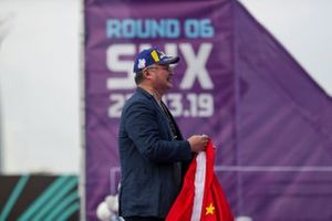 A DS TECHEETAH representative on the podium with a flag of the Peoples' Republic of China