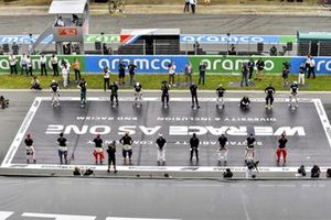 The drivers stand on the grid in support of the End Racism campaign