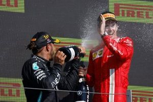 Lewis Hamilton, Mercedes, 1st position, and Charles Leclerc, Ferrari, 2nd position, celebrate with Champagne on the podium
