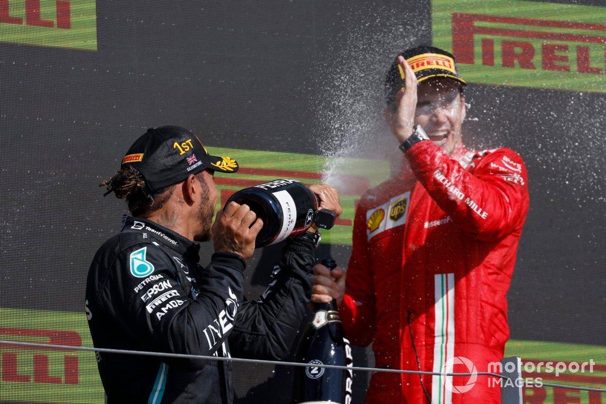 Lewis Hamilton, Mercedes, primo classificato, e Charles Leclerc, Ferrari, secondo classificato, festeggiano con lo Champagne sul podio
