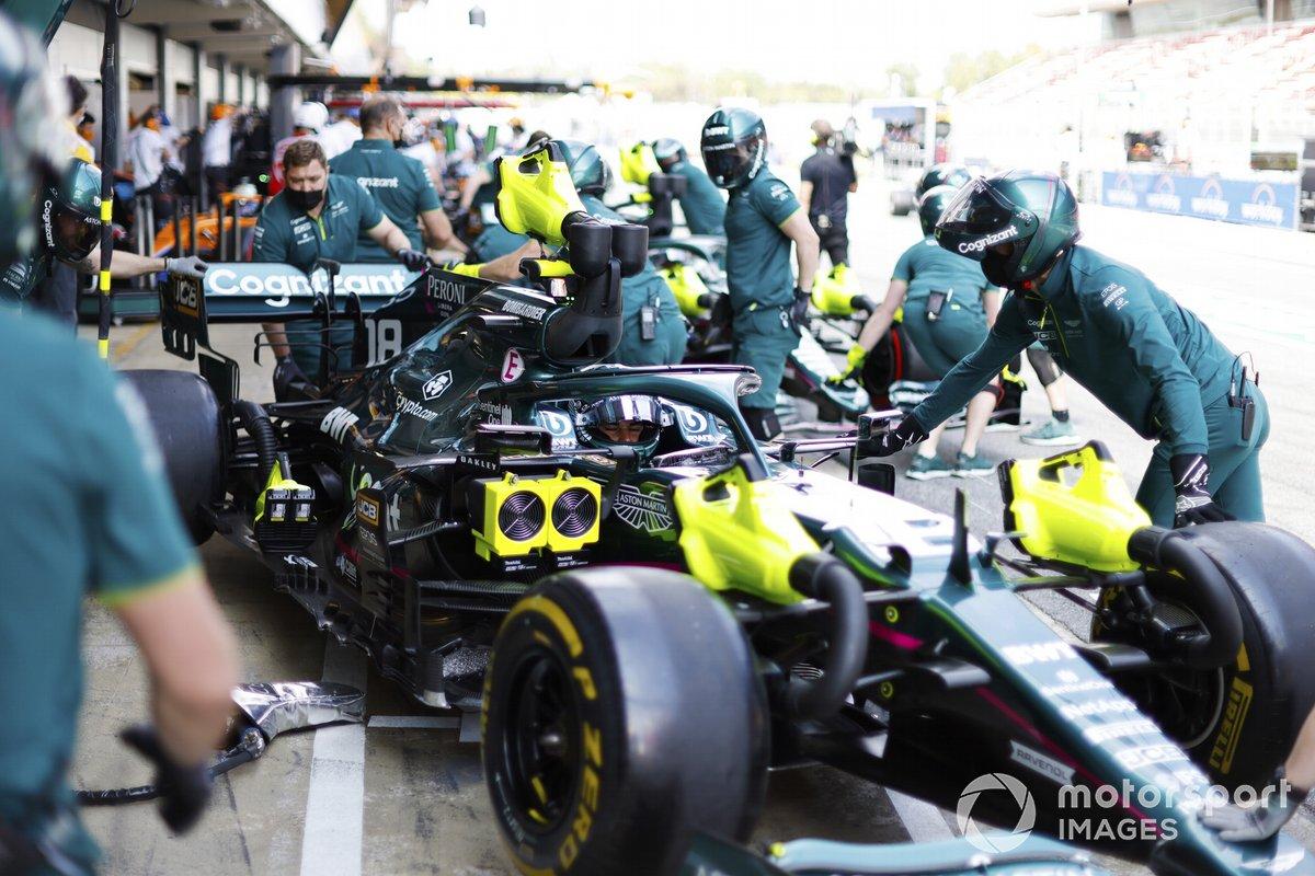 I meccanici riportano l'auto di Lance Stroll, Aston Martin AMR21, nel garage