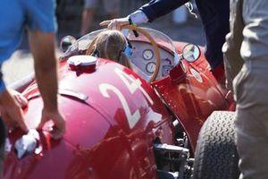 Une Maserati 250F est poussée dans le paddock avec une jeune personne dedans