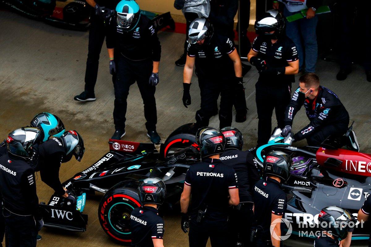 Miembros del equipo Mercedes trabajan en el coche de Lewis Hamilton, Mercedes W12, en el pit lane
