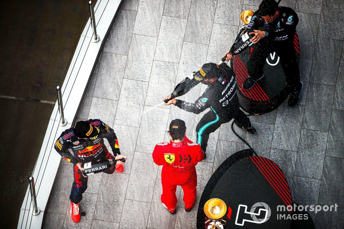 Max Verstappen, Red Bull Racing, 2a posizione, Carlos Sainz Jr., Ferrari, 3a posizione, il rappresentante del team Mercedes e Lewis Hamilton, Mercedes, 1a posizione, spruzzano Champagne sul podio