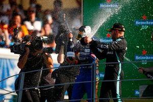 Daniel Ricciardo, McLaren, 1st position, and Valtteri Bottas, Mercedes, 3rd position, celebrate with Champagne on the podium
