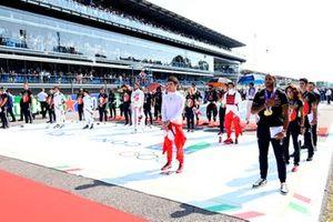 De coureurs staan op de startgrid met Italiaanse Olympische en voetbalhelden voor de start