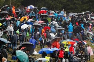 Fans under umbrellas during a red flag period