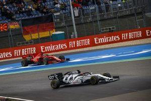 Daniil Kvyat, AlphaTauri AT01, passes as Sebastian Vettel, Ferrari SF1000, spins