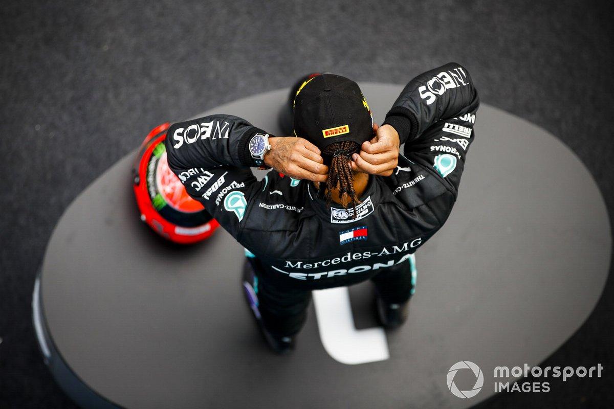 Lewis Hamilton, Mercedes-AMG F1, 1ª posición, en el podio con el casco de Michael Schumacher