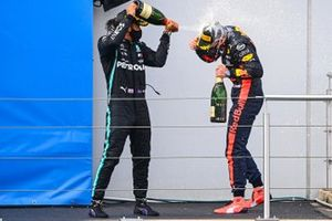 Lewis Hamilton, Mercedes-AMG F1, 1st position, and Max Verstappen, Red Bull Racing, 2nd position, celebrate on the podium with Champagne