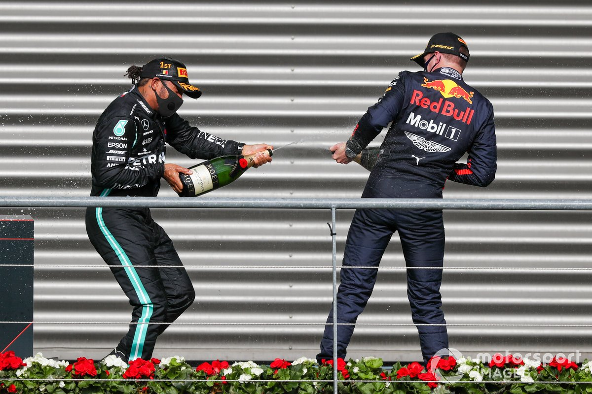 Lewis Hamilton, Mercedes-AMG F1, 1st position, and Max Verstappen, Red Bull Racing, 3rd position, spray Champagne on the podium