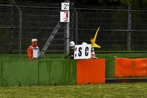Marshals deploy the Safety Car board and yelow flag