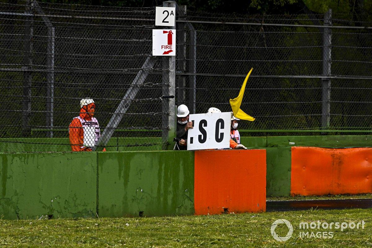 Los oficiales de pista despliegan el tablero del Safety Car y la bandera amarilla