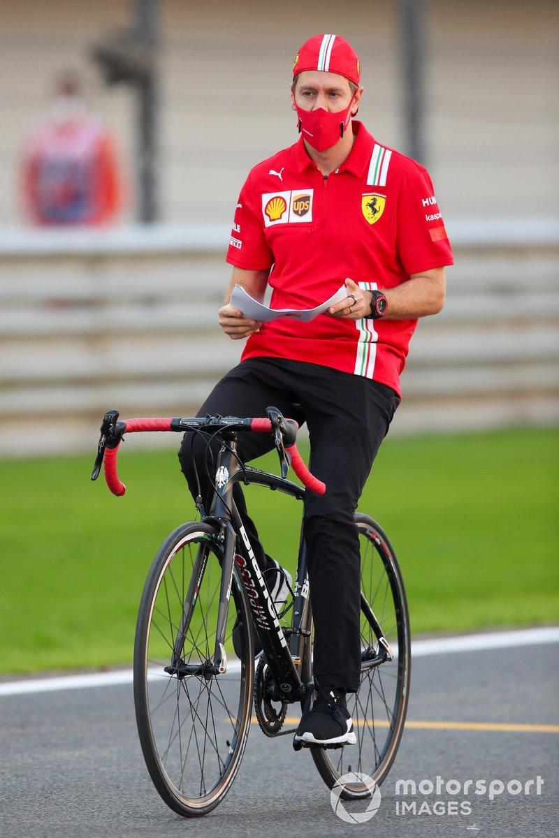 Себастьян Феттель, Ferrari, едет по трассе на велосипеде, рискуя упасть