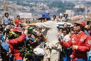 Podio: Carlos Pace celebra la victoria derramando champán sobre su compañero brasileño Emerson Fittipaldi, 2ª posición con Jochen Mass a la derecha, 3ª posición