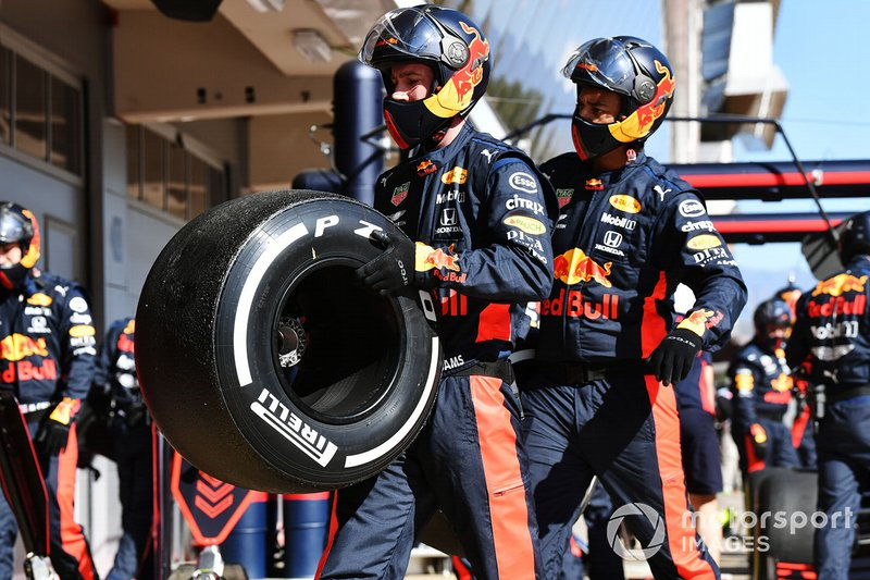 Red Bull mechanics carry a tyre after a pit stop