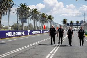 Mercedes team personnel walk the track