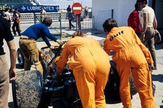Los mecánicos empujan el monoplaza de Bruce McLaren, McLaren M14A Ford a la pista