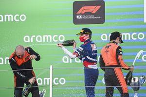 Robert Shwartzman, Prema Racing, 2nd position, and Nobuharu Matsushita, MP Motorsport, 1st position, celebrate with Champagne on the podium