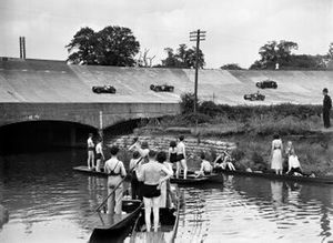 Boaters on the River Wey spectate as cars pass on the banking above them