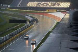 Safety Car and Medical Car driving round in heavy rain