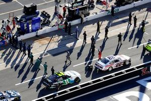 Drivers and crew stand for National Anthem before the race start