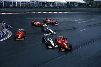 Michael Schumacher, Ferrari F300, collides with Mika Hakkinen, McLaren MP4/13 at the start