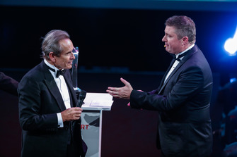 Jacky Ickx accepts a Gregor Grant Award on stage with David Croft