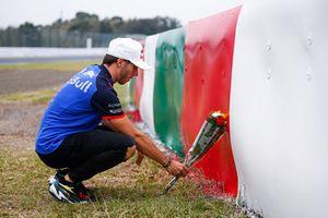 Гонщик Scuderia Toro Rosso Пьер Гасли возлагает цветы на месте аварии Жюля Бьянки