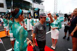 Fernando Alonso, McLaren, walks through a corridor of grid girls