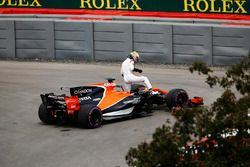 Fernando Alonso, McLaren, extracts himself from a leaking car in FP1