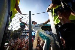 Lewis Hamilton, Mercedes AMG F1, takes a photo, fans