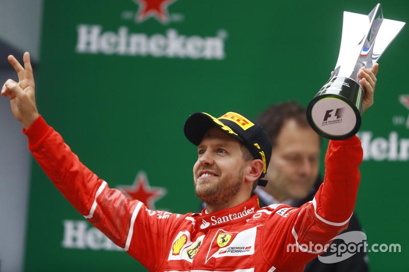 Sebastian Vettel, Ferrari, celebrates with his trophy on the podium