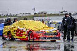 El auto de Joey Logano, Team Penske, Ford Fusion Shell Pennzoil, es empujado en el área de garajes bajo la lluvia.