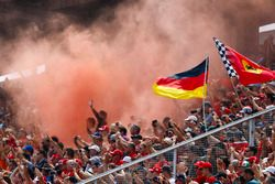 Fans in a grandstand set off flares
