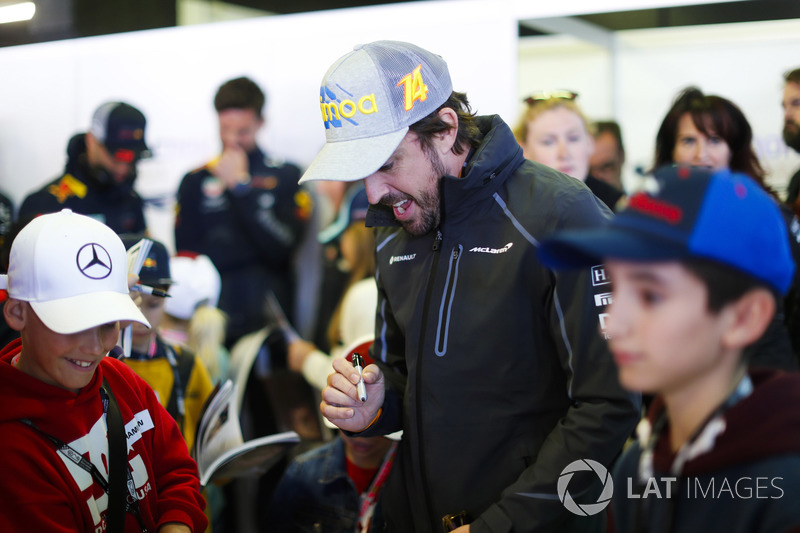 Fernando Alonso, McLaren, signs autographs for children