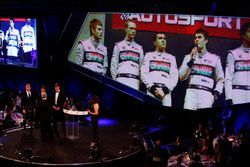 Derek Warwick receives an award from george Russell and Lando Norris. On the big screen is an image