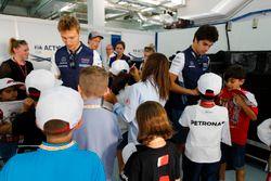 Sergey Sirotkin, Williams Racing, Lance Stroll, Williams Racing, et Brendon Hartley, Toro Rosso, signent des autographes pour des enfants