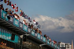 Fans watch from above the pit lane