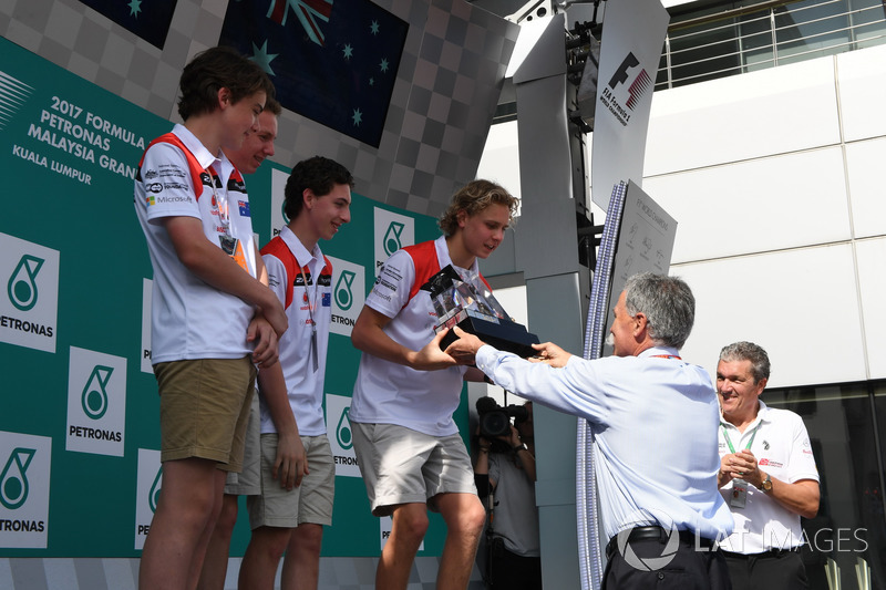 F1 in Schools students on the podium, Chase Carey, Chief Executive Officer and Executive Chairman of the Formula One Group and Andrew Denford, F1 in Schools