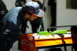 Fernando Alonso, McLaren, inspecciona su alerón trasero en el coche