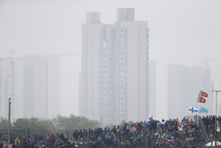 A gloomy skyline behind a grandstand full of fans