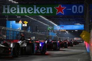 The cars pass the start line as the yellow flags are waved behind the Safety Car