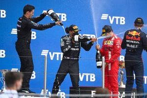 The Mercedes team representative, Lewis Hamilton, Mercedes, 1st position, Max Verstappen, Red Bull Racing, 2nd position, and Carlos Sainz Jr., Ferrari, 3rd position, spray Champagne on the podium